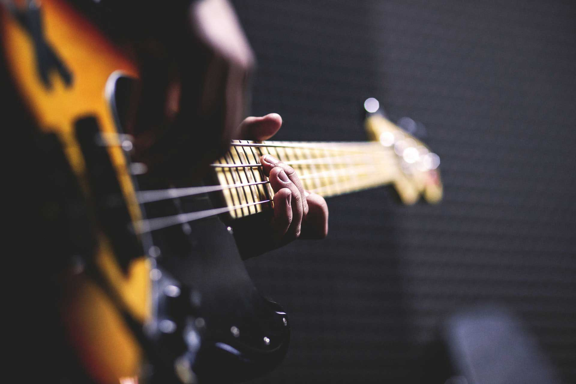 person-playing-sun-burst-electric-bass-guitar-in-bokeh-96380